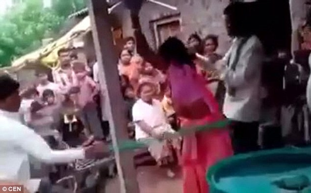 His wife, wearing traditional Indian dress, screamed as he whipped her and tried to move around the pole in a bid to escape the blows